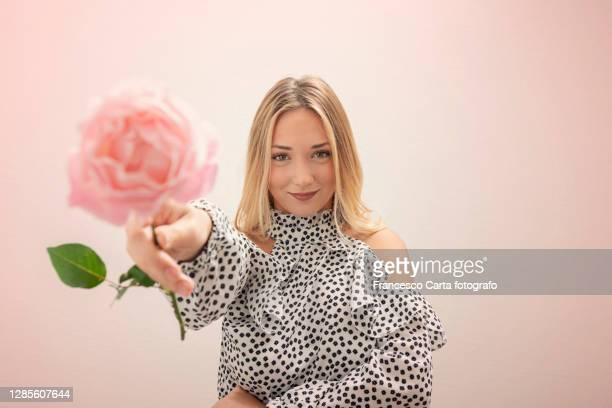 beautiful woman giving a pink rose - ナチュラルヘア ストックフォトと画像