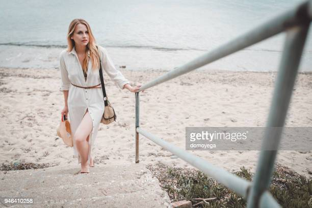 beautiful woman going up the stairs from the beach on a sunny summer day - sundress stock pictures, royalty-free photos & images