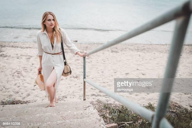 schöne frau, steigen die treppen vom strand an einem sonnigen sommertag - kleid stock-fotos und bilder