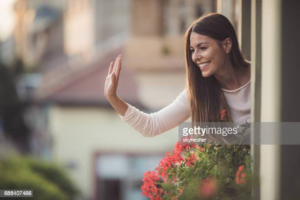 Beautiful woman greeting someone on the street from her house window.