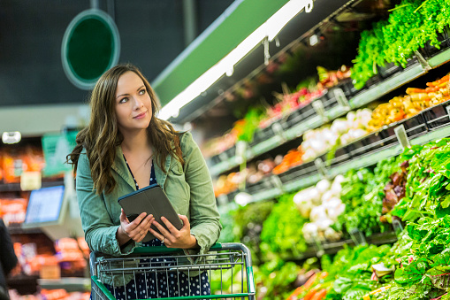 Beautiful woman grocery shopping with tablet - gettyimageskorea