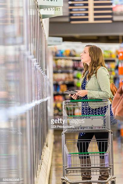 Beautiful woman grocery shopping with tablet