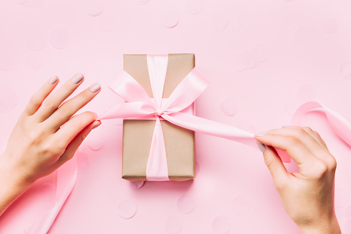 Beautiful woman hands with beautiful manicure open gift box. 1034353176