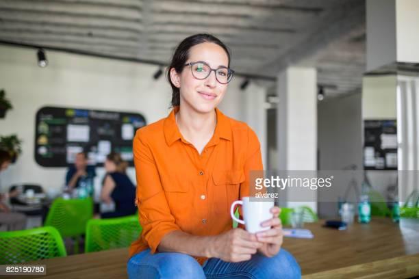 mooie vrouw met een koffiepauze bij het opstarten - 30 34 jaar stockfoto's en -beelden