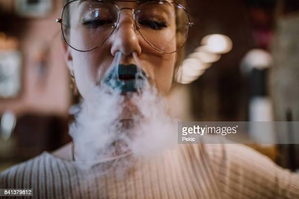 Beautiful woman having fun with smoke