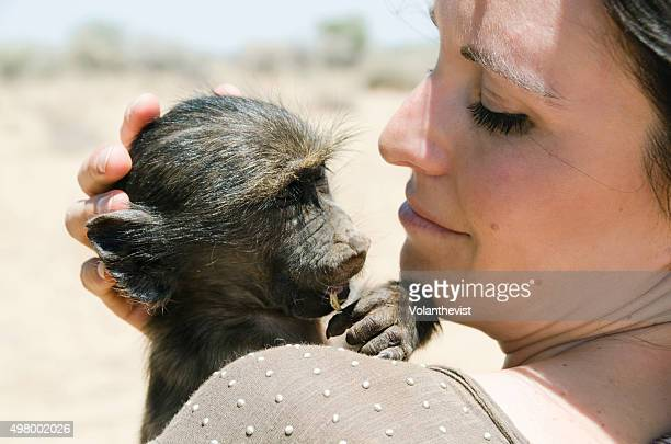 beautiful woman holding a baby baboon in namibia, southern africa - chacma baboon stock photos and pictures