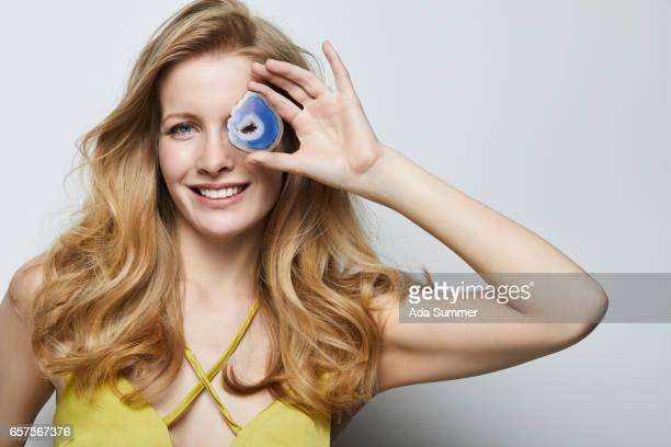 beautiful woman holding a blue colored agate gemstone in front of her face