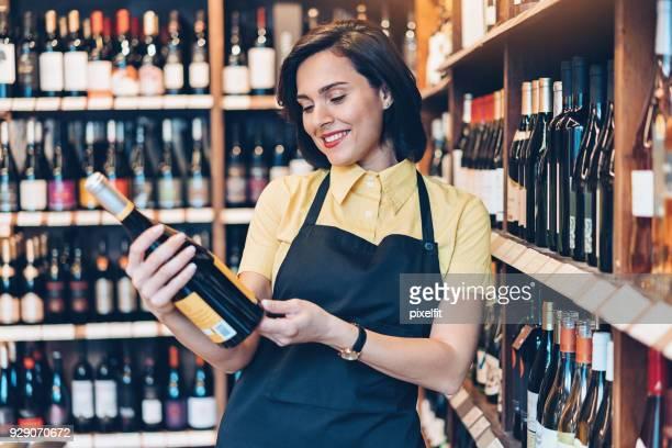 mooie vrouw met een fles rode wijn - alleen mid volwassen vrouwen stockfoto's en -beelden