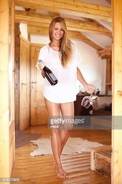 beautiful woman holding a bottle of wine and two glasses - women in slips stock photos and pictures