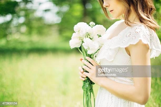 美しい女性の花束を持つ