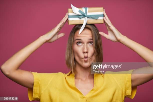 belle femme retenant un cadeau de noël - anniversaire humour photos et images de collection