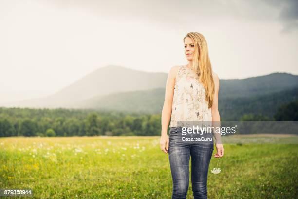 schöne frau, die eine blume und posiert auf wiese feld - junge frau allein stock-fotos und bilder
