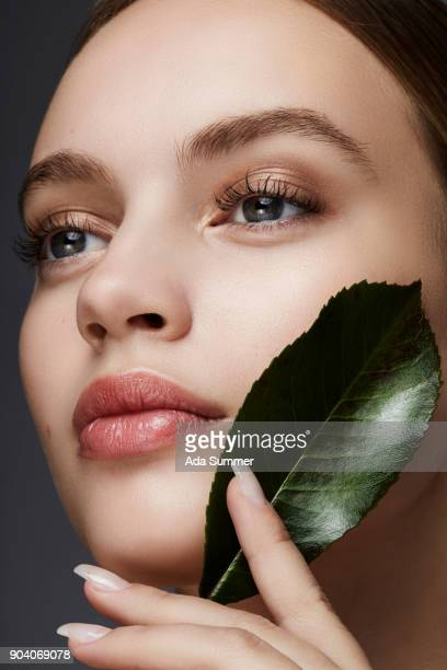 beautiful woman holding a green leaf on her cheek - pink lipstick stock photos and pictures