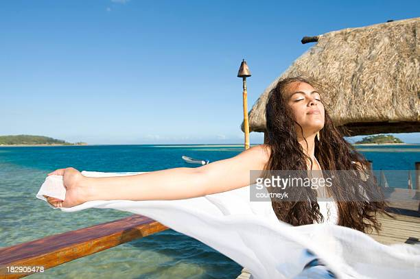 Beautiful woman holding a sarong being blown by the wind.