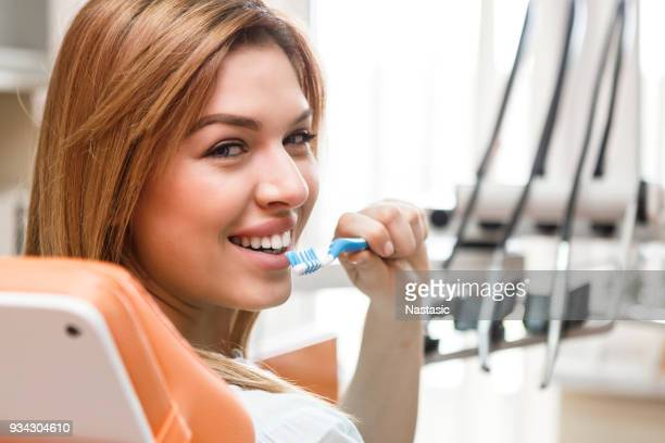 Beautiful woman holding a toothbrush at dentist
