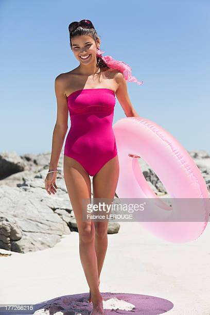 Beautiful woman holding an inflatable ring on the beach