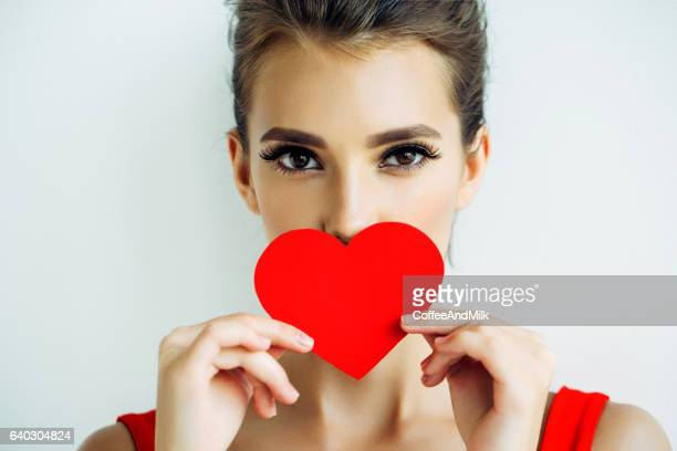 beautiful woman holding artificial heart - valentine's day stock photos and pictures