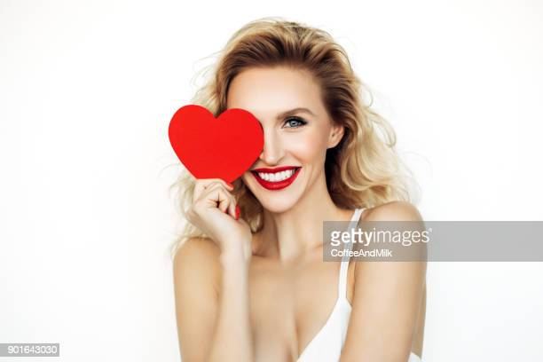 beautiful woman holding artificial heart - red lipstick stock photos and pictures