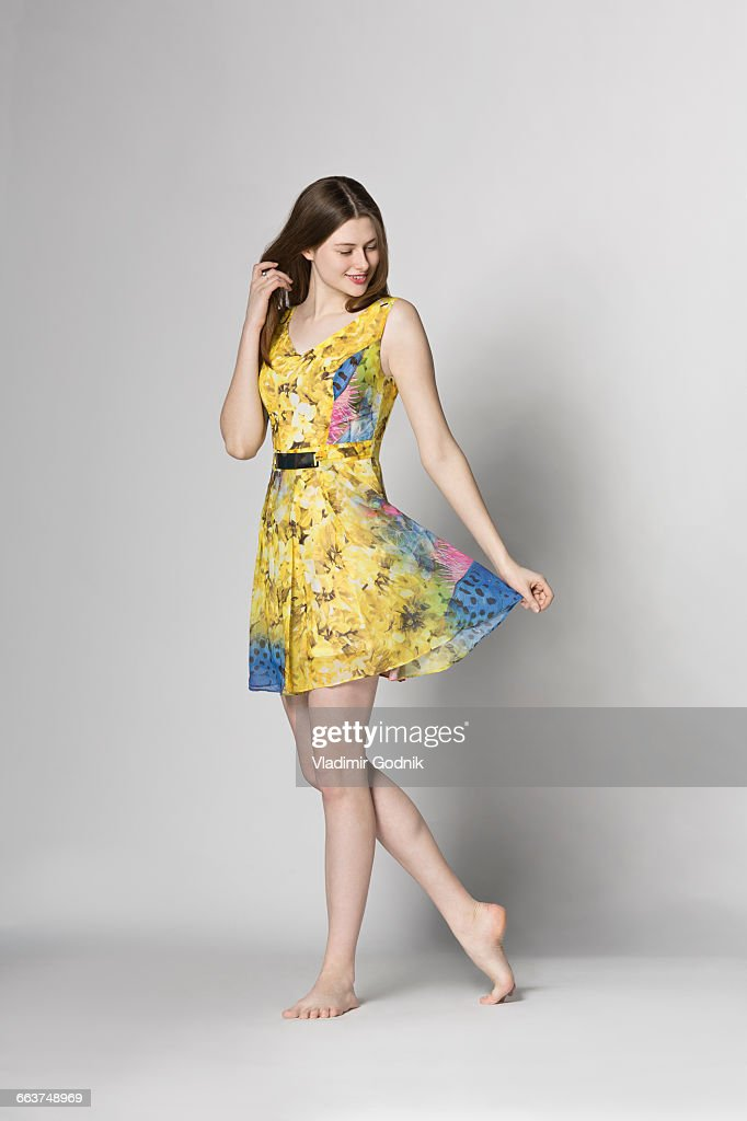 Beautiful woman holding dress while standing against white background : Stock-Foto