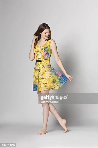 beautiful woman holding dress while standing against white background - vestido amarillo fotografías e imágenes de stock