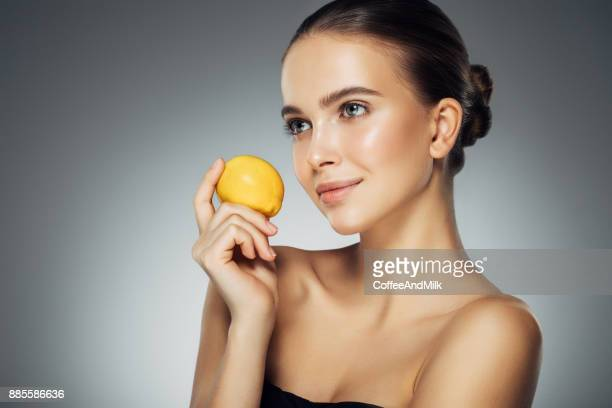 beautiful woman holding fresh lemon - acid stock photos and pictures
