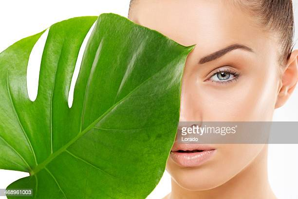beautiful woman holding green leaf - cosmetics stock pictures, royalty-free photos & images