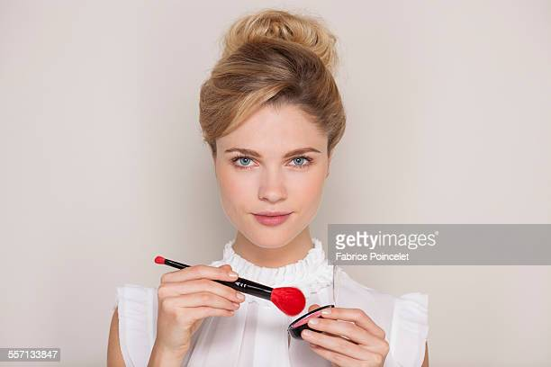 Beautiful woman holding make-up brush