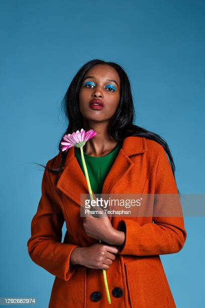 beautiful woman holding pink flower - purple coat stock pictures, royalty-free photos & images