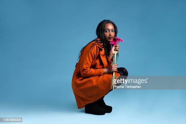 beautiful woman holding pink flower - secteur de la mode photos et images de collection