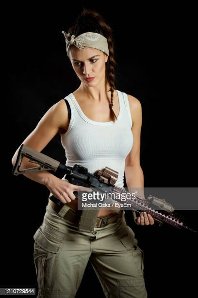 beautiful woman holding rifle standing against black background - ライフル ストックフォトと画像
