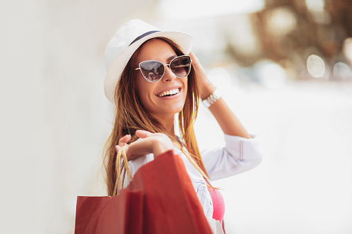 Beautiful woman holding shopping bags and smiling - outdoors 1047565898