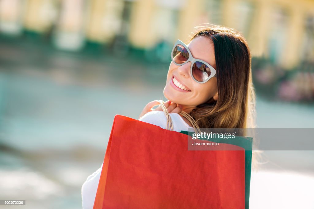 Beautiful woman holding shopping bags and smiling - outdoors : Stock Photo