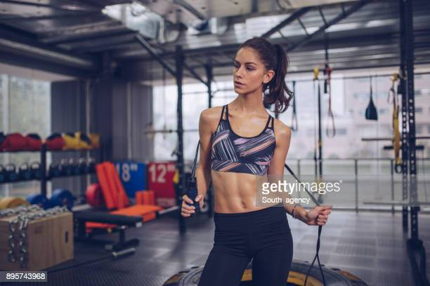 beautiful woman holding skipping rope in the gym - abdominal muscle stock pictures, royalty-free photos & images