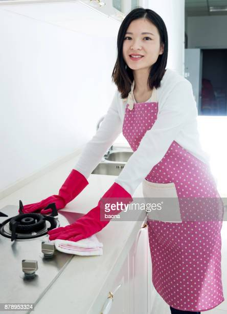 Beautiful woman holding spray bottle cleaning the kitchen stove