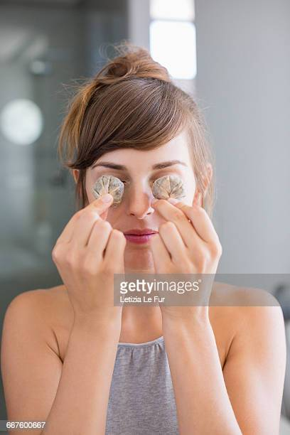 Beautiful woman holding tea bags in front of her eyes