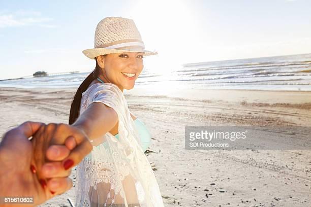 Beautiful woman holds husband's hand on the beach