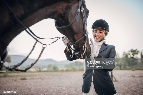 hermosa mujer jinete caballo acariciando a su caballo - evento ecuestre fotografías e imágenes de stock