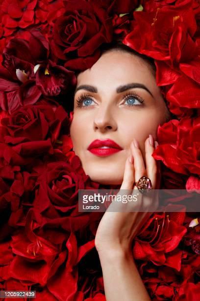 linda mulher em uma cama de flores vermelhas - dia da mulher - fotografias e filmes do acervo