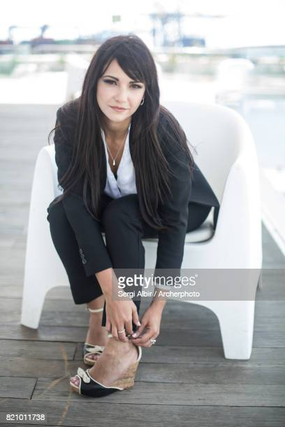 Beautiful woman in a black suit adjusting her shoe.