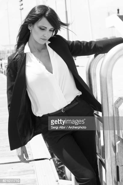Beautiful woman in a black suit hanging on a scale in the Port of Valencia
