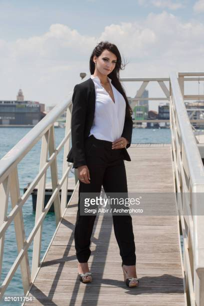 Beautiful woman in a black suit standing in the Port of Valencia.