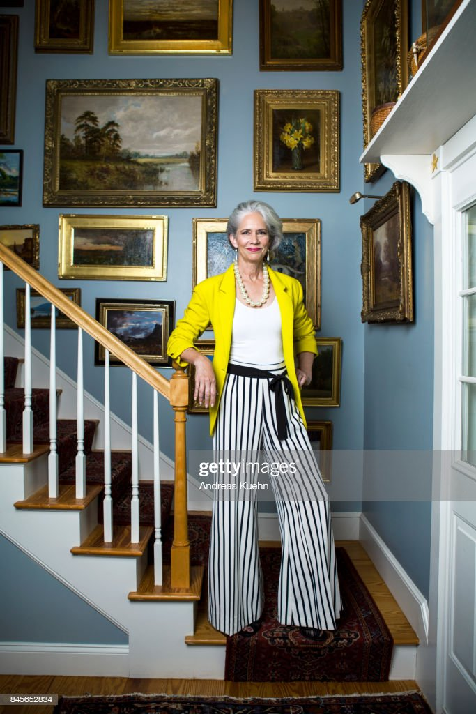 Beautiful woman in a fashionable outfit with silvery, grey hair standing in a staircase with golden framed oil painting on the wall. : Stock Photo
