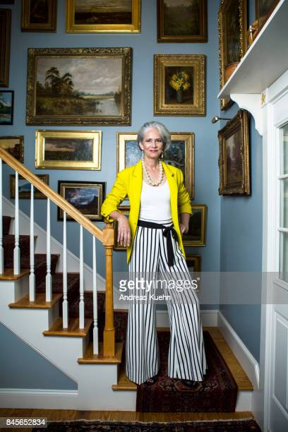 beautiful woman in a fashionable outfit with silvery, grey hair standing in a staircase with golden framed oil painting on the wall. - art dealer stock pictures, royalty-free photos & images