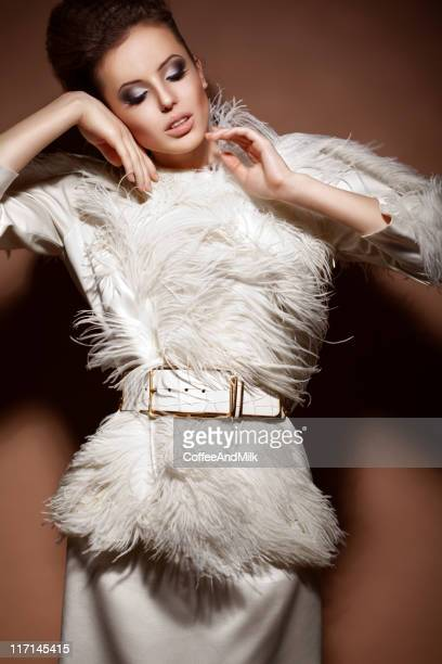Beautiful woman in a luxury dress with feathers