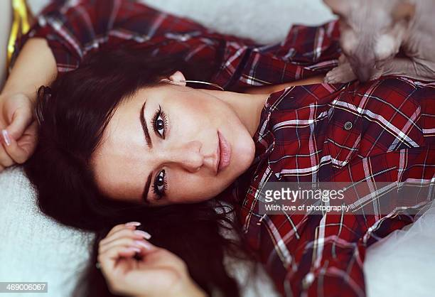 Beautiful woman in a plaid shirt with a sphinx cat
