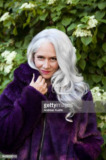 beautiful woman in a purple faux fur jacket with long, silvery, grey hair and a soft smile standing in front of white flowering ivy, close up. - gray coat stock pictures, royalty-free photos & images