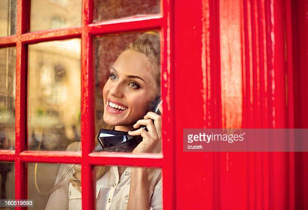 beautiful woman in a red telephone booth - telephone box stock pictures, royalty-free photos & images