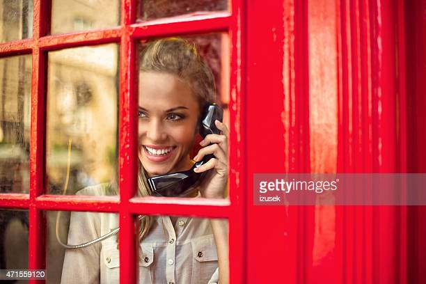 beautiful woman in a red telephone booth - red telephone box stock pictures, royalty-free photos & images