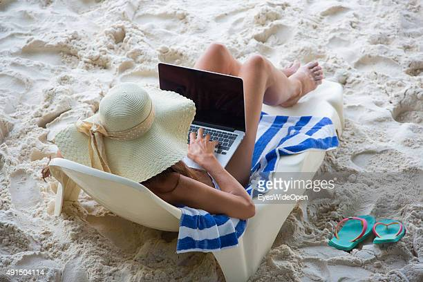 Beautiful woman in a white bikini working with a laptop at Patata beach on October 03 2015 in La Passe La Digue Seychelles