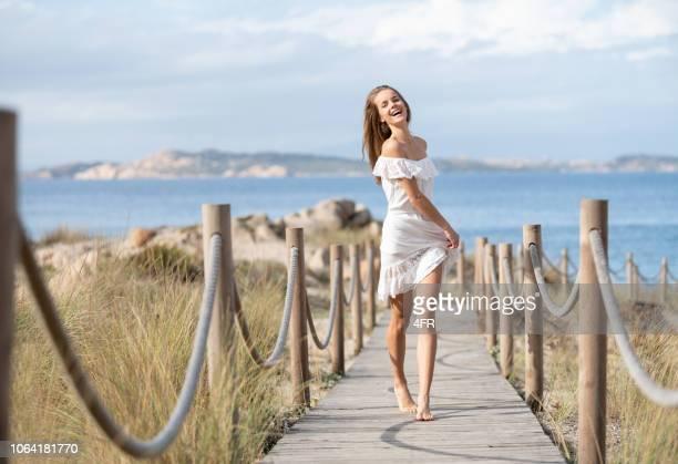 mujer hermosa en un vestido blanco con una perfecta expresión sincera caminando por un sendero enlazado a la playa, cerdeña, italia - cerdeña fotografías e imágenes de stock